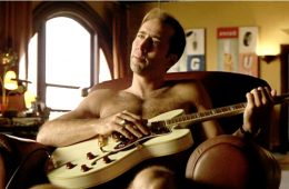 "The movie ""The Rock"", directed by Michael Bay. Seen here, Nicolas Cage (as Stanley Goodspeed),  unwinding at home, plucking a guitar. Theatrical release June 7, 1996. Screen capture. Copyright © 1996 Hollywood Pictures Company, Don Simpson Productions, Inc. and Jerry Bruckheimer, Inc. Credit: © 1996 Hollywood Pictures / Courtesy: Pyxurz."